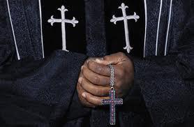 """African American Pastor holding cross"""