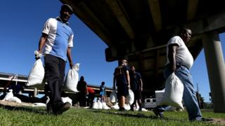 New Orleans residents fill up sand-bags under a road